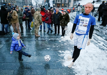 A boy kicks a ball at a mannequin of Russian President Vladimir Putin dressed in a football outfit as he takes part in a performance during a rally against Russia's hosting of the soccer World Cup this year, in Kiev