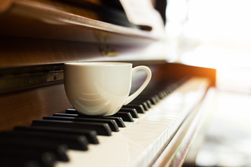 The white coffee cup put on blured piano key,in vintage warm light tone,blurry light around