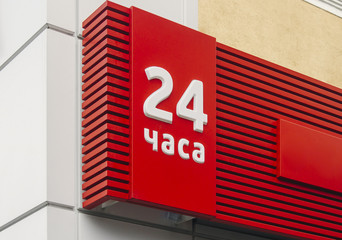 Photo of red 24 hour signboard isolated on wall background
