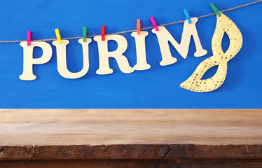 Purim celebration concept (jewish carnival holiday) in front of empty wooden table. product display backdrop.