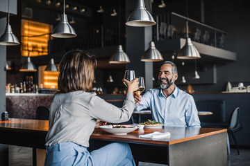 Man and woman drinking wine at restaurant.