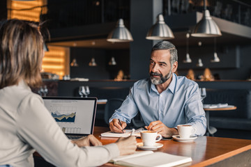 Businessman talking with his colleague in coffee shop