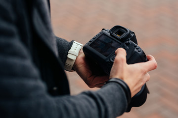 Photographer holding professional camera looks at photos, outdoors. Close-up.
