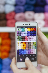 blogger woman taking a picture of a set of woolen yarns