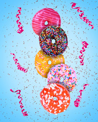 colorful doughnuts with icing covered with sprinkles and chocolate pieces on a blue background with confetti and streamers
