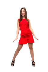 Sexy carefree girl in red dress in stockings and in high heels shoes is standing with her legs wide apart isolated on white background.