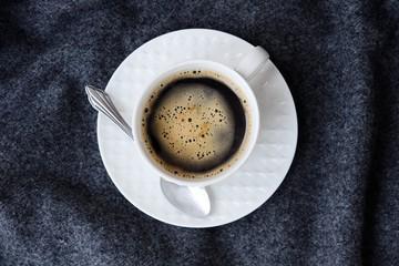 Delicious fresh tasty coffee on grey plaid