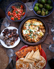 Traditional morocco Tajine dishes, morocco salat, bread and dry fruit on the table. High angle view on realistic morocco meal.