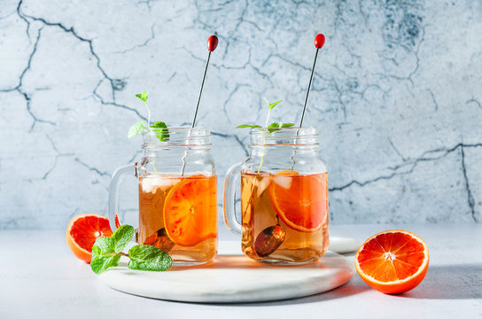 Traditional iced tea with orange and mint and ice in mason jars . refreshing summer drink on white marble board with orange and mint and ice in mason jars . refreshing summer drink