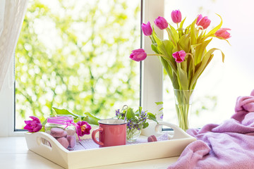 Cozy home concept. Purple fresh tulips in glass vase. Macaroons in glass jar. Cup of hot tea. White tray. Lilac blanket on the windowsill. Sunshine. Coloring and processing photo
