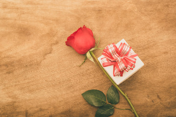 Flat lay image of Valentines Day Background with Gift Box and Red Rose on Wood Table Rustic style
