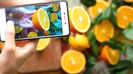 Hands Taking Photo of Oranges.