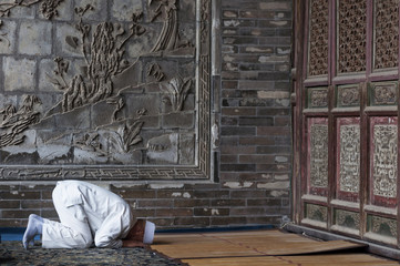 One man praying at the Xi'An Great Mosque in the city of Xi'An in China, Asia.