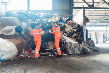Two workers in recycling facility standing in front of a garbage heap to be sorted
