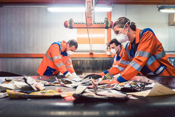 Workers in sorting room of garbage recycling facility