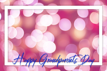 Hand-painted Happy Grandparents Day lettering surrounded by a white frame on a natural background with fuzzy lights in a shade of pink