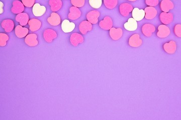 Candy sugar hearts top border on a pastel purple paper background