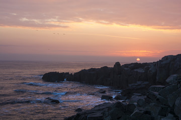 Sunrise, sunset, rocks, sea and pink clouds