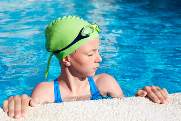 Portrait of little cute child in the swimming pool.Focussed athlete before the start