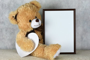 A loving teddy bear keeps a frame with a heart on the day of Saint Valentine's Day