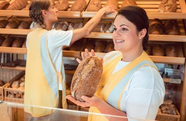 Verkäuferinnen verkaufen Brot und Brötchen beim Bäcker, sie arbeiten als Team zusammen
