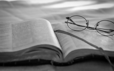Reading old bible and glasses sitting outdoors in black and white
