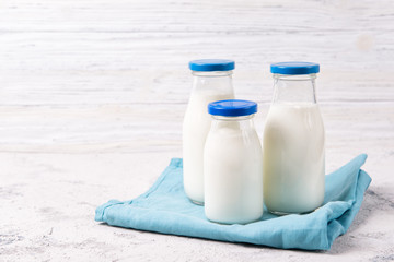Three bottles of milk on a table, wooden background