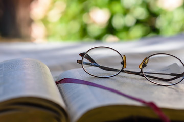 Close up glasses resting on open bible outdoors with room for text