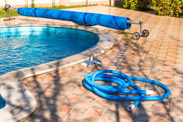 Manual equipment for cleaning pool, brush, hose, swimming pool cover, Yesulskaya, Krasnodar, Russia. Copy space for text.