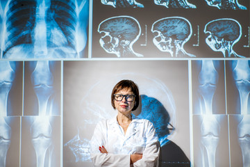 Portrait of a senior woman doctor in uniform with projected x-rays of human parts