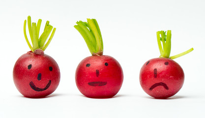 Three red radishes with painted faces showing emotions on a white background