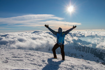 Young happy tourist on top of a snowy mountain enjoying valley view, above the clouds. Conceptual design.