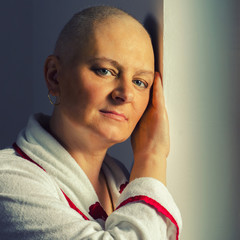 Bald woman suffering from cancer standing beside hospital window.