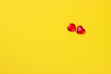 Valentines day concept two red hearts on yellow background.