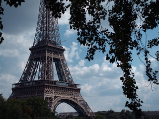 Lower section of the Eiffel Tower seen from the New York Avenue and framed by tree branches during one summer Parisian afternoon against a cloudy blue sky