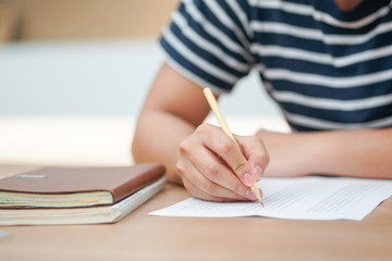 close up man hand choose some choice in answer sheet in library room before test , educational concept