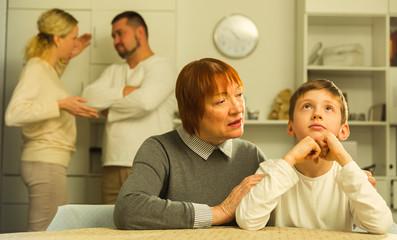 Grandma hugging upset boy during parental quarrel