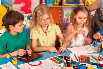 Child dough play in school. Plasticine for children. mold from plasticine in kindergarten .Kids knead modeling clay with hands in preschool. Children's childhood hobby of drawings in classrooms.