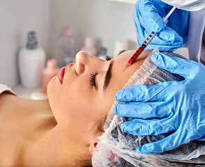 Filler injection for woman forehead face. Plastic aesthetic facial surgery by doctor in beauty clinic. Doctor in medical gloves with syringe. Wellbeing medical removing wrinkles .