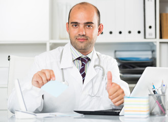 Smiling therapist in uniform filling up documents