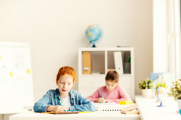 Two little classmates sitting by individual desks and carrying out teacher task
