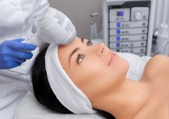 The doctor-cosmetologist makes the procedure Cryotherapy of the facial skin of a beautiful, young woman in a beauty salon.Cosmetology and professional skin care.