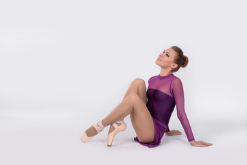 the ballerina in pointes and a violet dress sits on a white background
