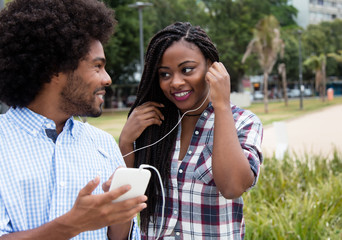 African american woman enjoys music with hipster friend