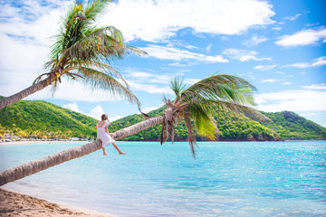 Adorable little girl sitting on palm tree during summer vacation on white beach Wall mural