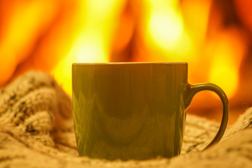 Green mug for tea or coffee, wool things near cozy fireplace, winter vacations.