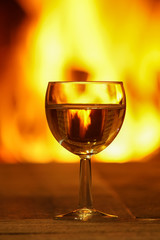 Glass of white wine against cozy fireplace background, winter vacation.