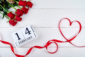 Valentines Day background with red ribbon shaped as heart, bouquet of roses and wood block calendar february 14 on white wood table, copy space for text. Love, wedding concept. Top view, flat lay