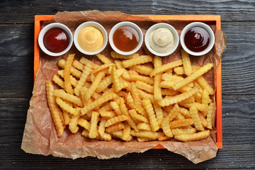 French fries on big wooden tray with sauces
