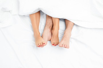 Close up of the feet of a couple on the bed.